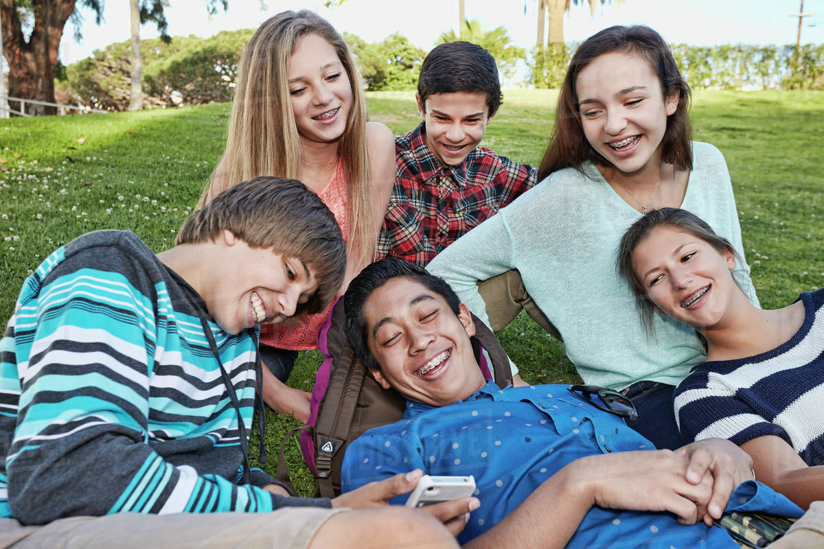 Teenagers relaxing together in grass Royalty-free stock photo