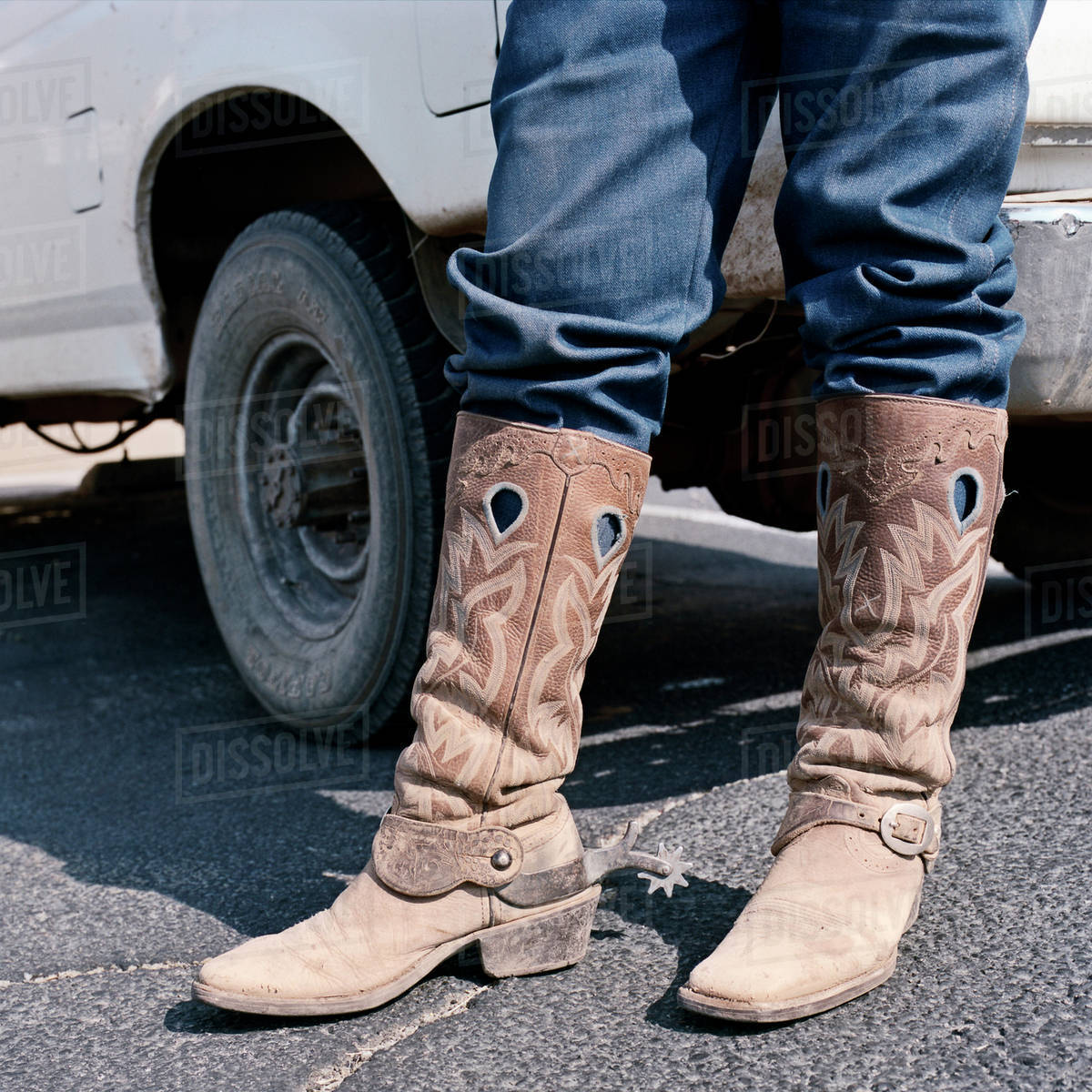 Close up of man wearing cowboy boots with spurs stock photo