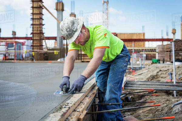 Construction worker finishing concrete at construction site Royalty-free stock photo
