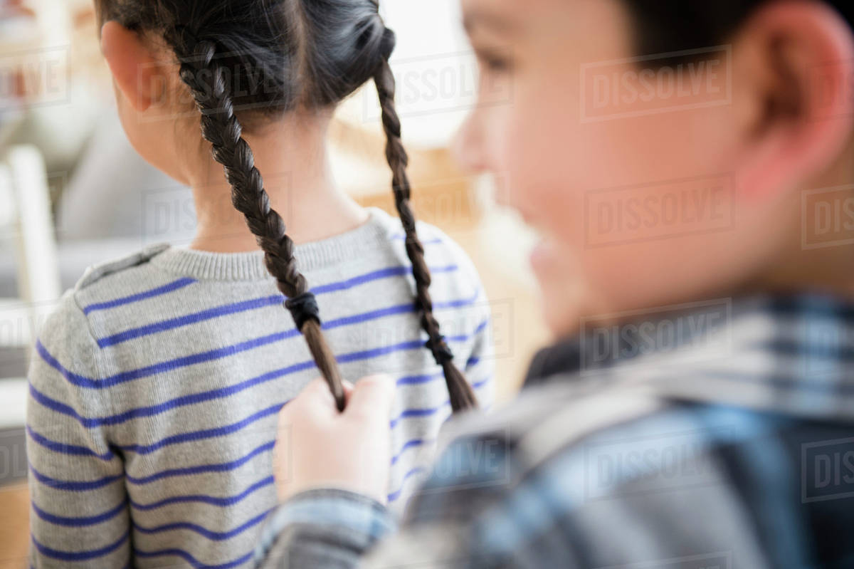 Boy pulling girl's pigtails Royalty-free stock photo