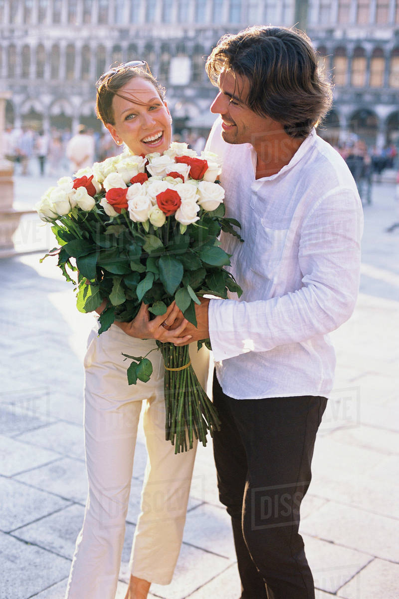 Man giving girlfriend flowers on city street - Stock Photo - Dissolve
