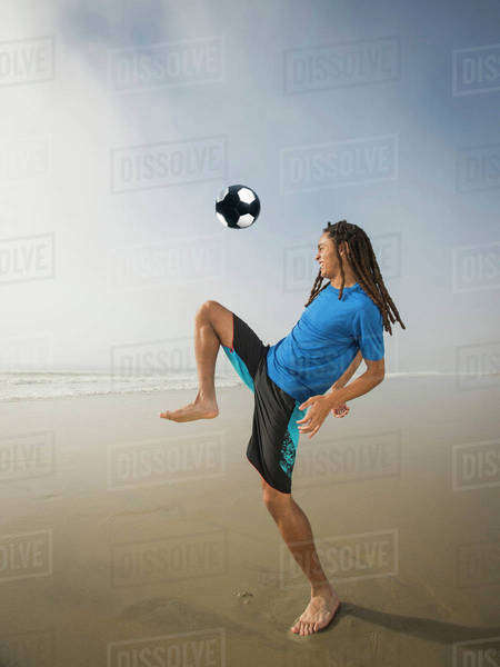 Black teenage boy playing with soccer ball on beach Royalty-free stock photo