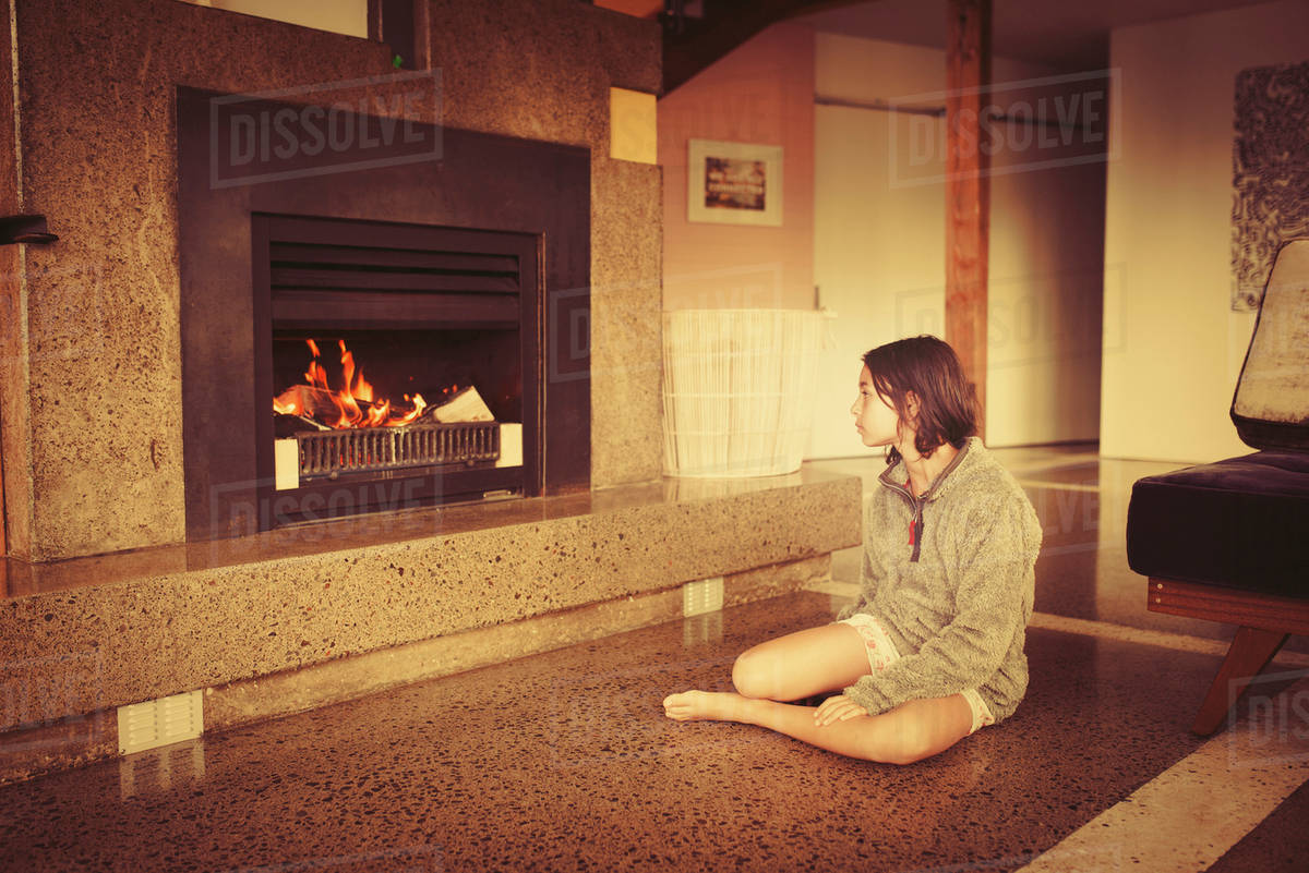 Mixed race girl relaxing by fireplace in living room stock photo