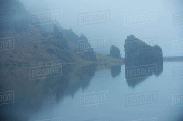 Rock formations and remote misty lake Royalty-free stock photo