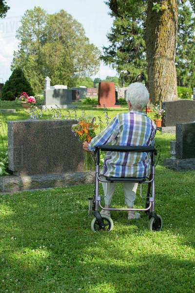 Older Caucasian woman visiting grave in cemetery Royalty-free stock photo