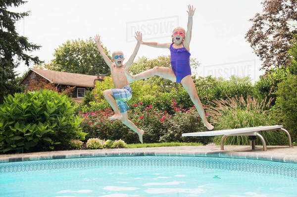 Caucasian children jumping into swimming pool Royalty-free stock photo