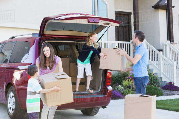 Caucasian family unpacking cardboard boxes from car Royalty-free stock photo