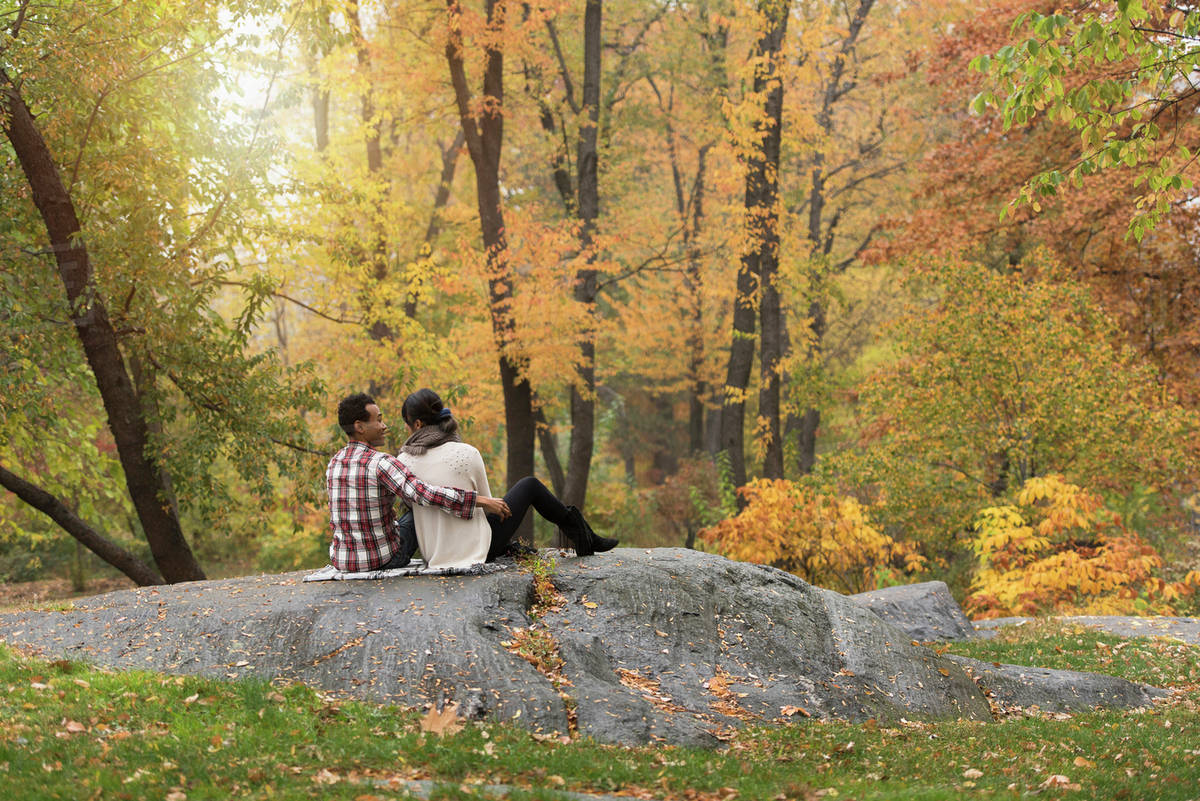 Asian couple hugging on rock in park Royalty-free stock photo