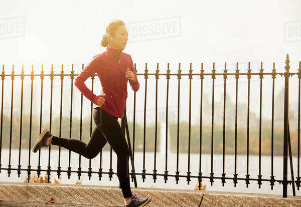 Asian woman running on waterfront path Royalty-free stock photo