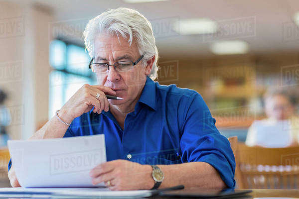 Man reading paperwork in library Royalty-free stock photo