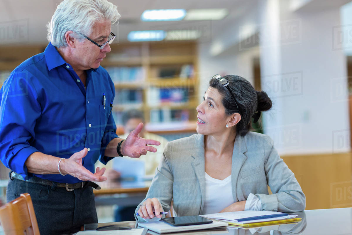 Teacher helping adult student in library Royalty-free stock photo