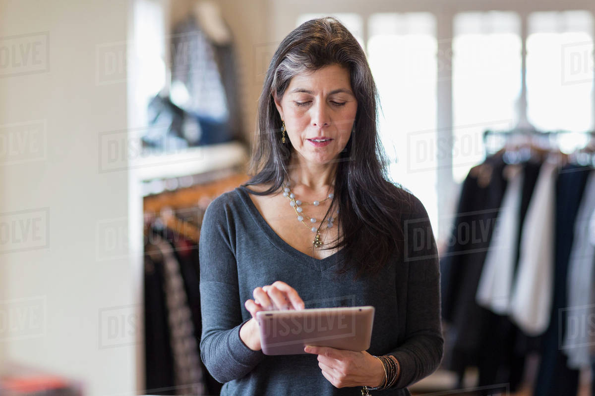 Hispanic small business owner using digital tablet in store Royalty-free stock photo