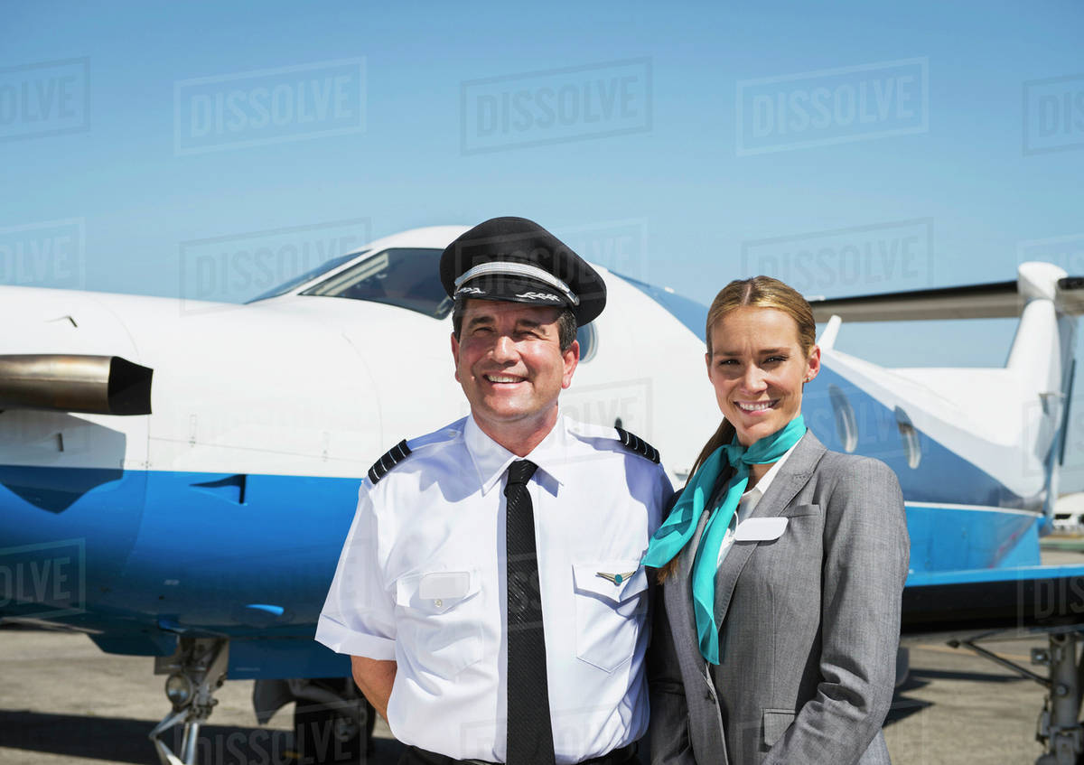 Caucasian pilot and flight attendant smiling on runway stock photo