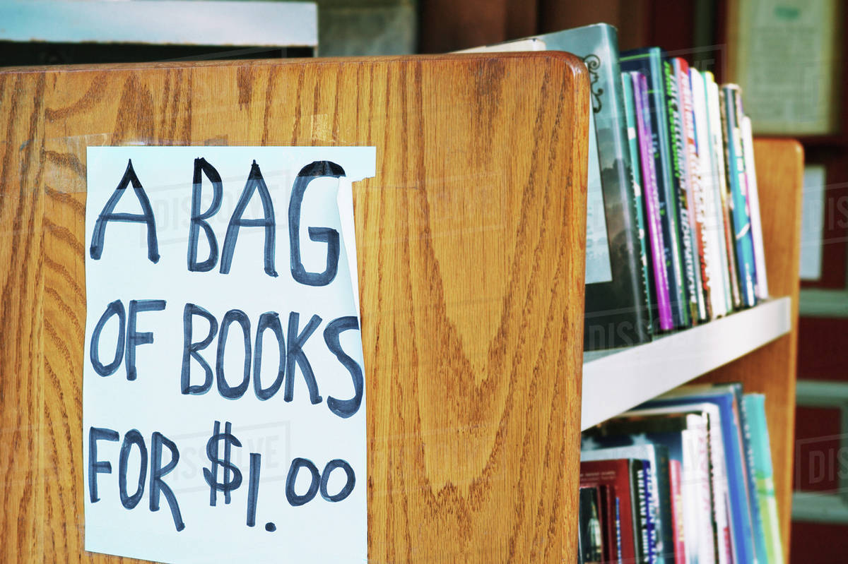 a bag of books for 1 00 sign in library stock photo dissolve
