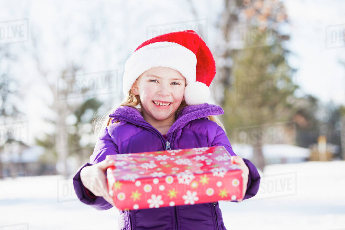 79911ea4a3532 Caucasian girl in Santa hat holding Christmas present - Stock Photo ...