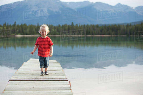 Caucasian boy walking on dock over remote lake Royalty-free stock photo