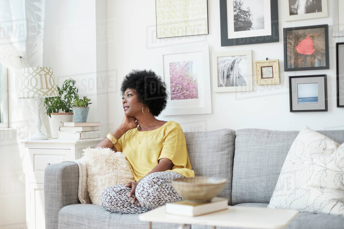 African American woman relaxing on sofa - Stock Photo - Dissolve