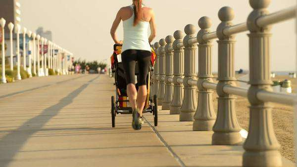 Caucasian mother jogging on boardwalk with baby stroller Royalty-free stock video