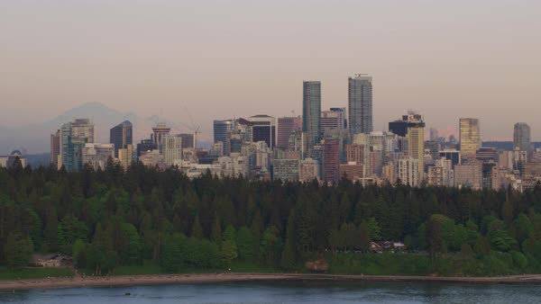 Aerial shot of Vancouver cityscape with modern buildings, trees in foreground, British Columbia, Canada Rights-managed stock video