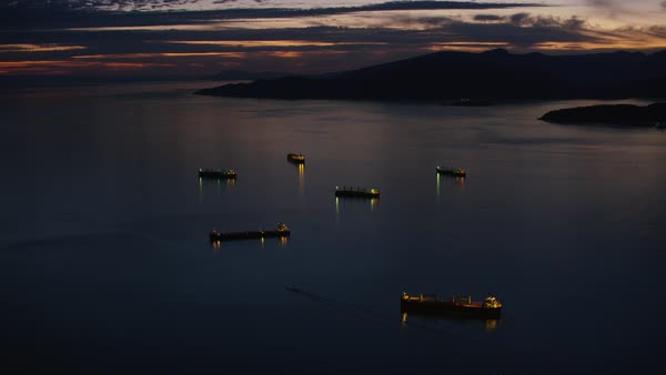 Aerial shot of barge moving in sea at sunset, silhouetted mountain in background, Vancouver, British Columbia, Canada Rights-managed stock video