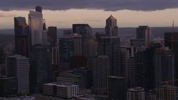Aerial shot of modern Seattle cityscape at dusk, Elliott Bay in background, Washington, United States of America Rights-managed stock video