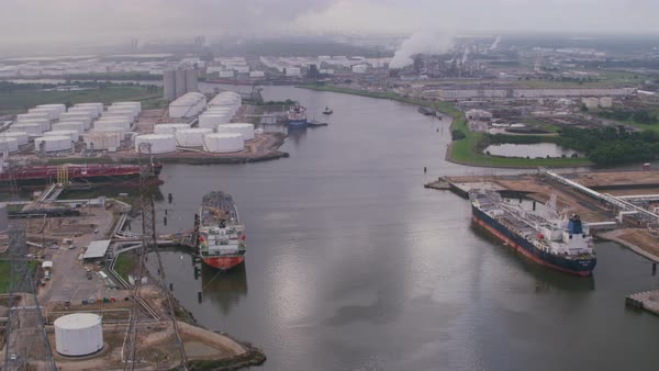 Cargo ships moored at Houston Ship Channel with storage tanks of refinery, Houston, Texas, United States of America Rights-managed stock video