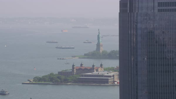 Aerial shot of Statue of Liberty and Ellis Island seen from behind a skyscraper Rights-managed stock video