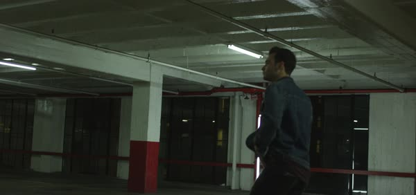 Hand-held shot of a man walking in a parking garage Royalty-free stock video