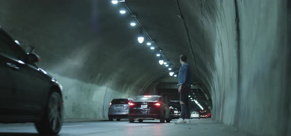 Hand-held shot of a man watching cars driving by in a tunnel Royalty-free stock video