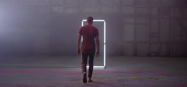Slow motion shot of a man walking towards a frame made of tube lights Royalty-free stock video