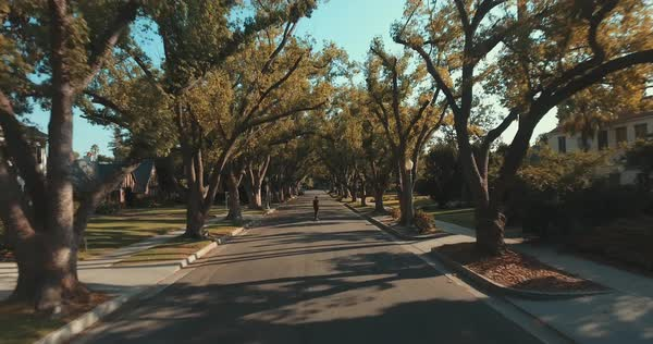 Drone shot of a man skateboarding on a suburban street Royalty-free stock video