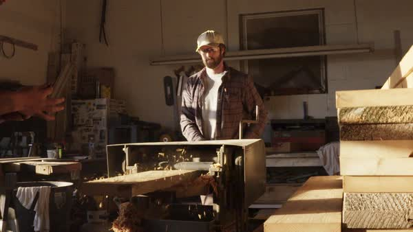 Slow motion shot of two men planing a wooden plank with a planer Royalty-free stock video