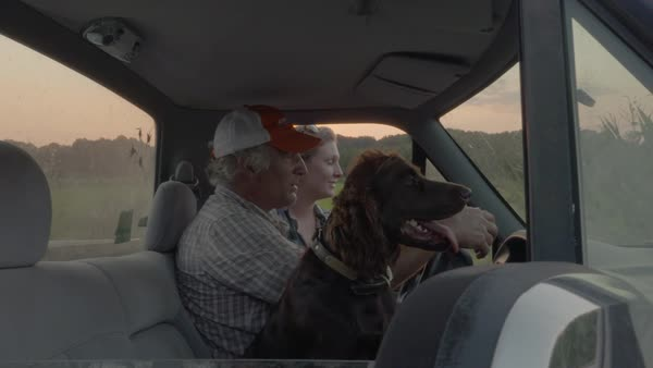 Panning shot of a man talking with a woman while sitting with his dog in a truck Royalty-free stock video
