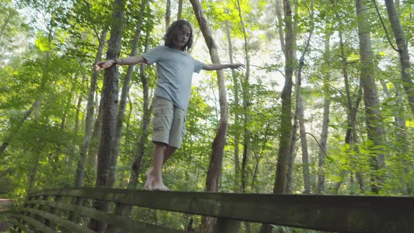 Hand-held shot of a boy walking on railing of a bridge in a forest Royalty-free stock video