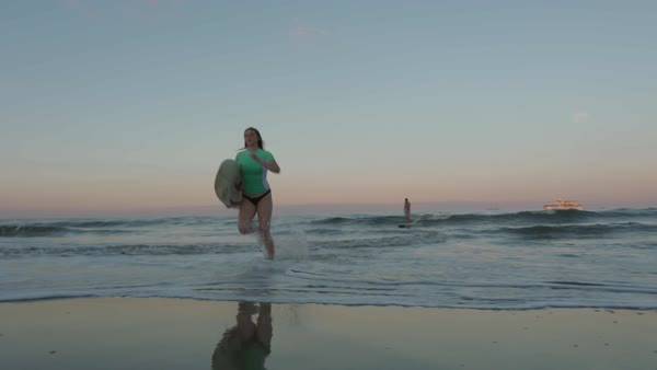 Slow motion shot of a young woman running out of sea with a surfboard Royalty-free stock video