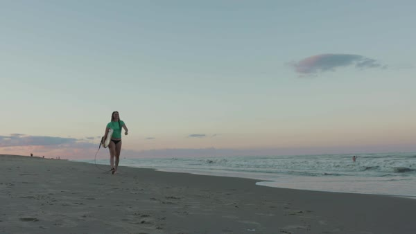 Hand-held shot of a woman walking on a beach with a surfboard Royalty-free stock video
