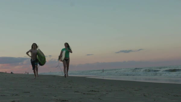 Hand-held shot of a woman and a boy running on a beach with surfboards Royalty-free stock video