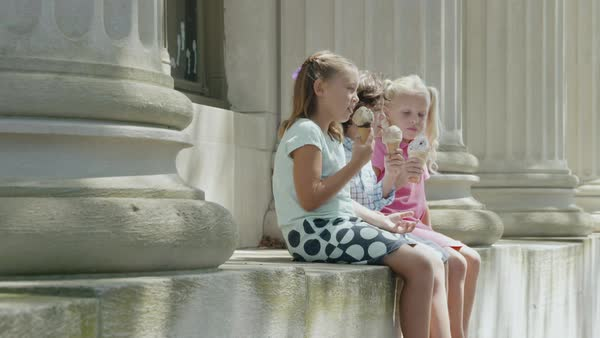 Slow motion shot of three children eating ice cream while sitting between two pillars Royalty-free stock video