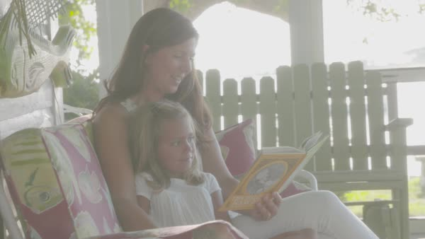 Slow motion shot of a mother reading a book to her daughter Royalty-free stock video