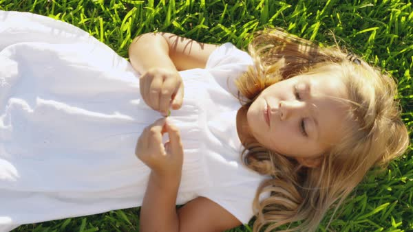 Hand-held shot of a girl playing with a blade of grass Royalty-free stock video
