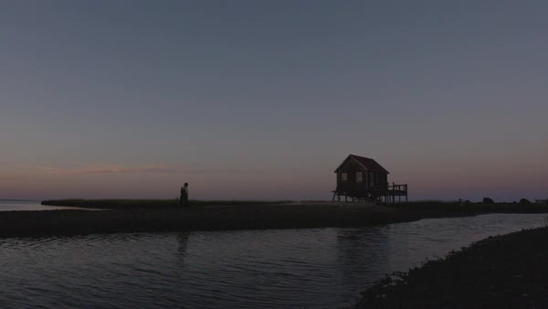 Hand-held shot of a fisherman walking to a stilt house on a seashore Royalty-free stock video