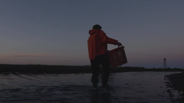 Static shot of a fisherman walking in water with a basket of oysters Royalty-free stock video