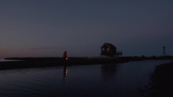 Hand-held shot of a fisherman walking to a stilt house with a lantern Royalty-free stock video