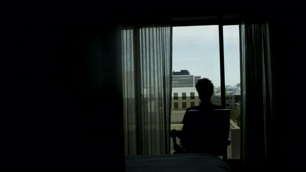 Man sitting in a chair and looking through a window Royalty-free stock video