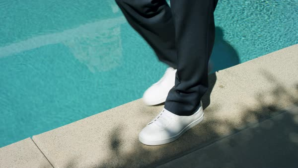 Slow motion shot of a man wearing sneakers walking on edge of a swimming pool Royalty-free stock video