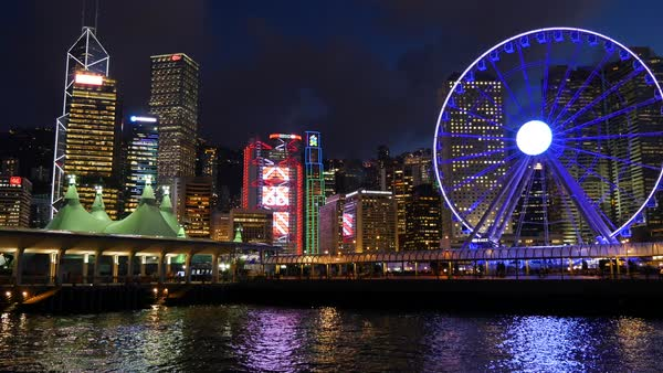 A wide shot of a city scape in Hong Kong during night time, with a large Ferris wheel. Royalty-free stock video