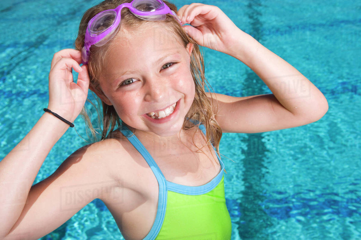 2d5cbf2a67 Young girl adjusting goggles next to swimming pool - Stock Photo ...