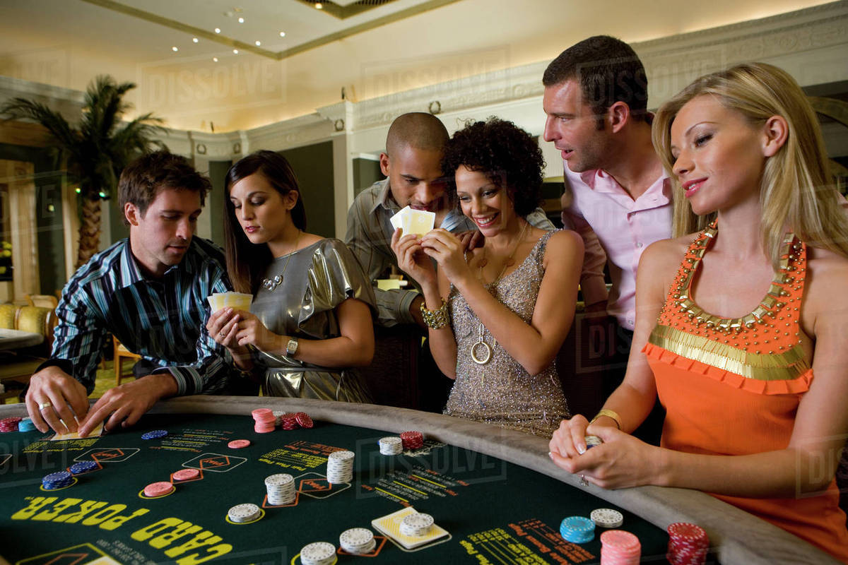 Young men and women gambling at poker table in casino, smiling - Stock  Photo - Dissolve