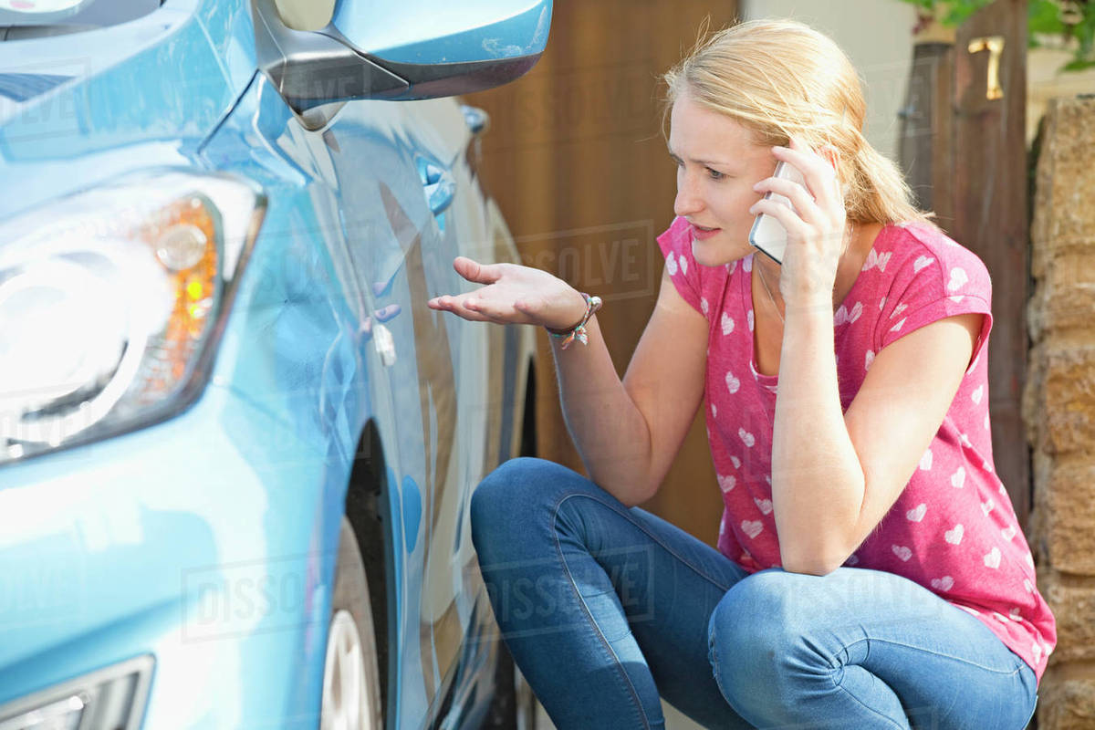 Woman Phoning Insurance Company To Report Car Damage