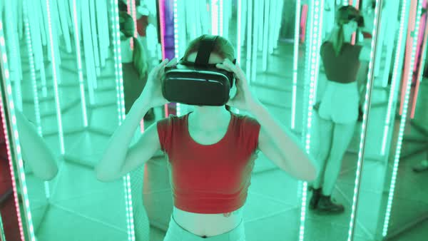Young woman wearing VR goggles in mirrored room Royalty-free stock video
